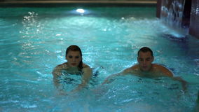 Young couple swimming in pool stock footage