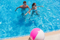 Young Couple in Swimming Pool with Beach Ball Royalty Free Stock Image