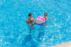Young Couple in Swimming Pool with Beach Ball Stock Photography