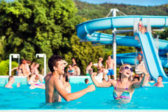 Young couple in swimming pool on sunny day. Water slide. Royalty Free Stock Photos