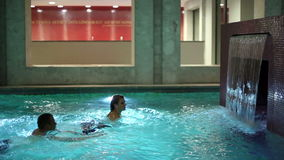 Young couple swimming in pool with waterfall and underwater lights stock video footage