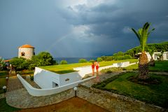 Young Couple Watching the Storm Sky with a Beatiful Rainbow Over the Sea in a Greek Hotel royalty free stock photos