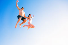 Young Couple In Swimwear Jumping Royalty Free Stock Images