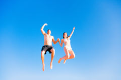 Young Couple In Swimwear Jumping Royalty Free Stock Photos