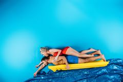 Young couple in swimwear swimming on inflatable mattress. On blue stock photography