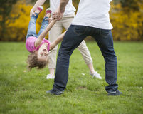 Young couple swinging daughter between them Stock Photo
