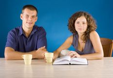 Young couple at the table with book Royalty Free Stock Image