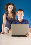 Young couple at the table with laptop Stock Photography
