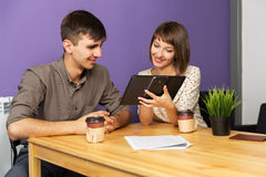Young couple with tablet computer sitting at the table Royalty Free Stock Photography