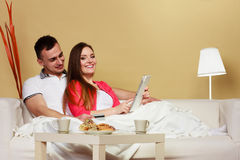 Young couple with tablet and credit card at home Stock Image