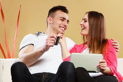 Young couple with tablet and credit card at home Stock Images