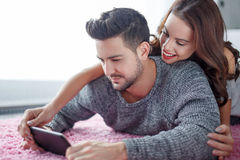 Young couple with tablet lying prone on carpet online shopping. Young couple with tablet lying prone on carpet, wi-fi technology, online shopping Royalty Free Stock Images
