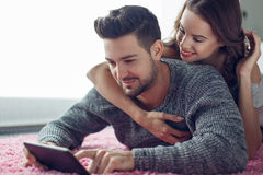 Young couple with tablet lying prone on carpet Stock Photo