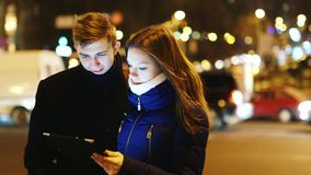 Young couple with a tablet in the night traffic stock video footage