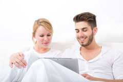 Young couple with a Tablet PC in Bed Royalty Free Stock Photo