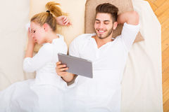 Young couple with a tablet PC in bed Royalty Free Stock Image