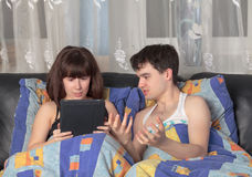 Young couple with tablet PC in their bed royalty free stock photos