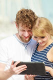 Young couple with tablet by seaside outdoor Royalty Free Stock Photo