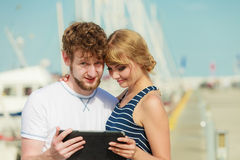 Young couple with tablet by seaside outdoor Stock Photo