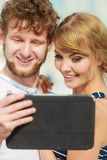 Young couple with tablet by seaside outdoor Royalty Free Stock Photos