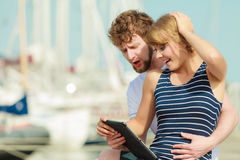 Young couple with tablet by seaside outdoor Stock Images