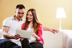 Young couple with tablet sitting on couch at home Stock Photos