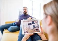 Young couple with tablet sitting on sofa, looking at interior design sketches. A young couple with tablet sitting on sofa, looking at interior design sketches stock photo