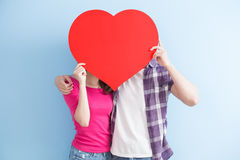 Young couple take heart. Young couple take love heart on blue background stock photo