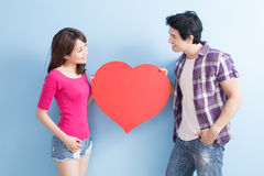 Young couple take heart. Young couple take love heart on blue background stock photos