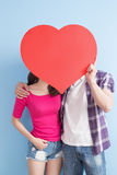 Young couple take heart. Young couple take love heart isolated on blue background stock image