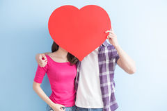 Young couple take heart. Young couple take love heart isolated on blue background royalty free stock photos