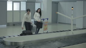 Young couple take out the luggage from conveyor belt in the airport. The action takes place at the arriving hall of the airport near the baggage claim desk stock video footage