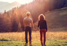 Young couple takes hands in sunset time. Young couple at the sunset time on the mountain slope Royalty Free Stock Photos