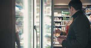Young couple taking frozen food from fridge in the. Young people choosing food in fridge section of the supermarket. Woman taking two packages of frozen stock video footage