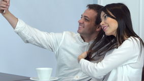Young couple taking funny selfies on the phone in a cafe. Close up shot. Professional shot on Lumix GH4 in 4K resolution. You can use it e.g. in your stock footage