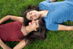 Young couple taking a nap on green grass Royalty Free Stock Images