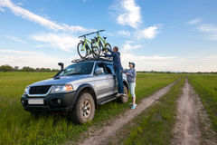 Young couple taking off their bicycles from roof rack Royalty Free Stock Photo