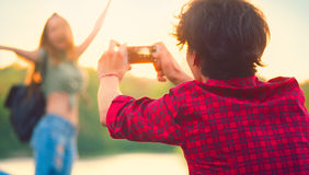 Young couple taking photo on smartphone. Happy joyful young couple taking photo on smartphone, walking in summer park together Royalty Free Stock Photos