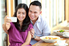 Young couple taking a photo of them using mobilephone camera Royalty Free Stock Photo
