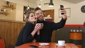 Young couple taking a photo of themselves in a cafe. stock footage