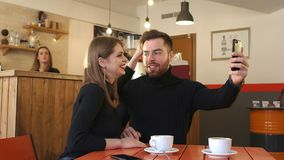 Young couple taking a photo of themselves in a cafe. Happy couple enjoying a coffee at the coffee shop. Happy couple sitting in the cafe and taking a selfie stock video