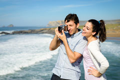 Young couple taking photo to the sea Royalty Free Stock Photo