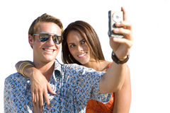 Young couple taking photograph of themselves, woman embracing man, smiling, cut out. Young couple taking photograph of themselves, women embracing man, smiling Royalty Free Stock Image