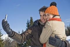 Young couple taking photos on the snow Royalty Free Stock Photography