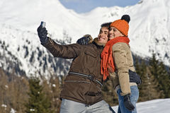 Young couple taking photos on the snow Royalty Free Stock Images
