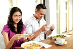 Young couple taking photos of their food Royalty Free Stock Photography