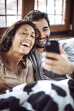 Young couple taking photos of themselves, making crazy faces. Royalty Free Stock Photo