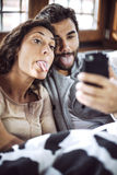 Young couple taking photos of themselves, making crazy faces. Royalty Free Stock Photography
