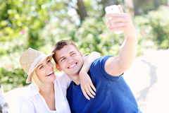 Young couple taking a picture of themselves at the beach Royalty Free Stock Photography