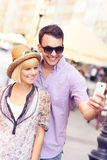 Young couple taking picture of themselves while sightseeing the Royalty Free Stock Photos